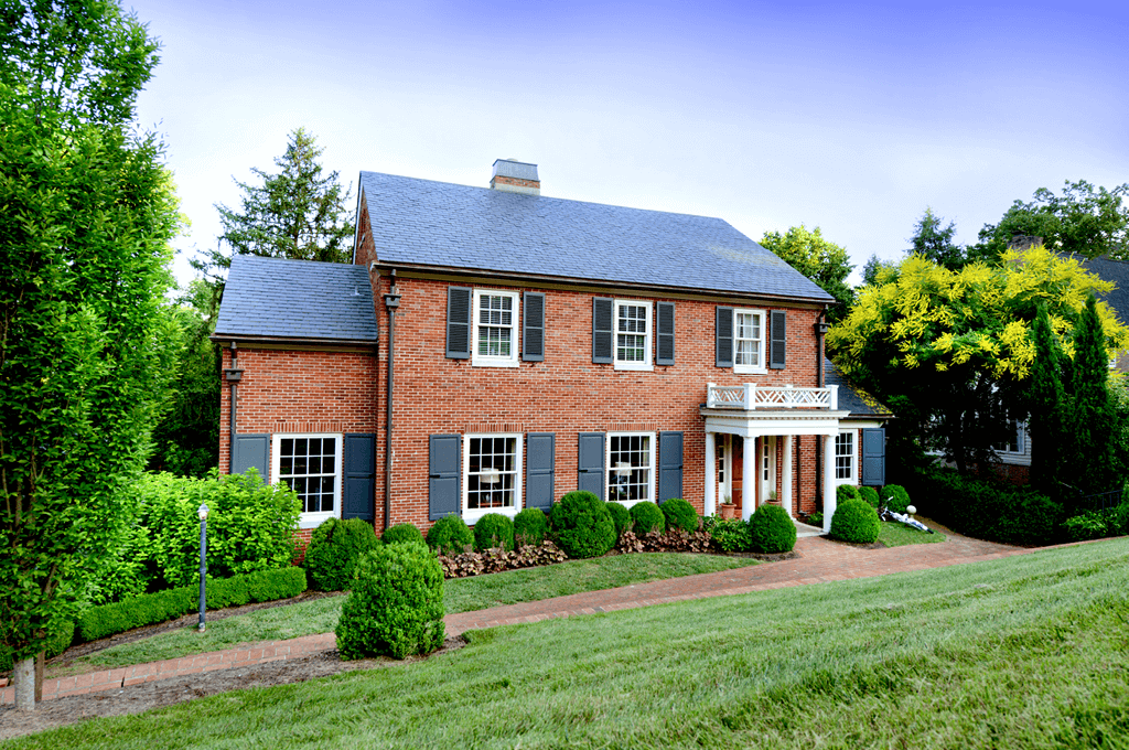 red brick home with Adorned Openings composite wood panel and louver shutters and shutter hardware