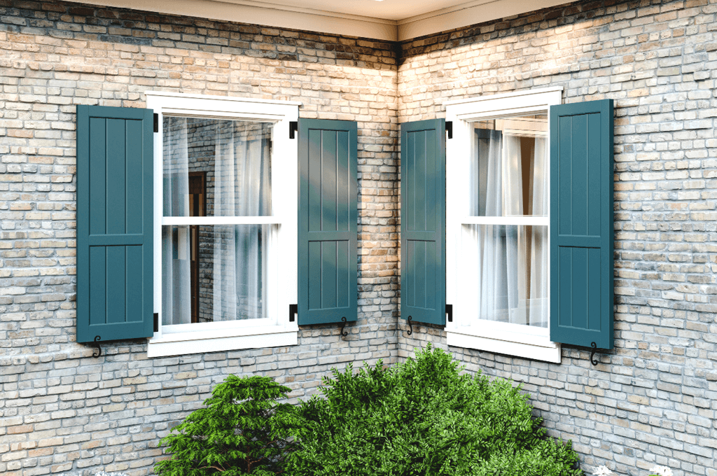 blue Adorned Openings closed board & batten shutters on brick home with functional shutter hardware