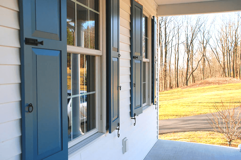 two pairs of Adorned Openings raised panel shutters with shutter locks, pull rings and tiebacks