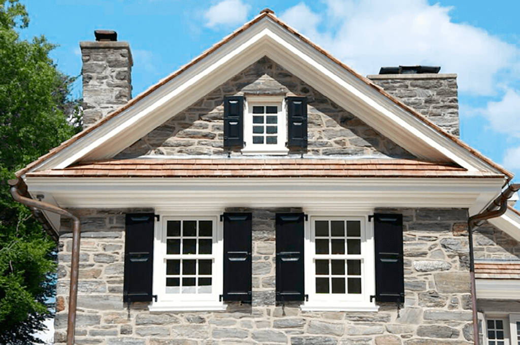 black Adorned Openings panel shutters installed on stone home with functional shutter hardware