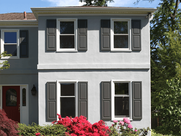 gray stucco home with gray panel shutters with neatly trimmed landscaping