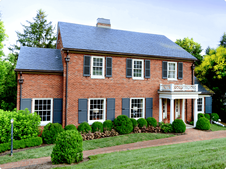 red brick home with blue panel and louver style shutters with shutter hardware